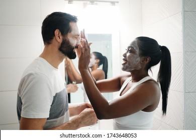 Frauen, die Schönheitsmaske und Hautreiniger auf den Menschen anwenden