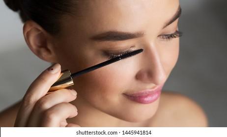 Woman Applying Black Mascara on Eyelashes with Makeup Brush, Grey Background
