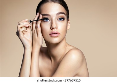 Woman applying black mascara on eyelashes with makeup brush / photos of appealing brunette girl on beige background