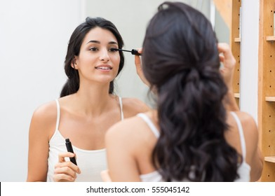 Woman applying black mascara on eyelashes with makeup brush. Young beautiful woman applying mascara makeup on eyes at bathroom. Beautiful brunette girl applying makeup on eyes in the morning time.