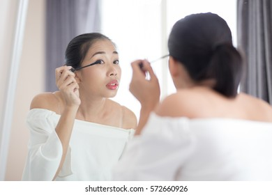 Woman applying black mascara on eyelashes with makeup brush looking to the mirror