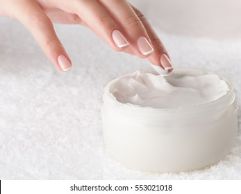 Woman applying body cream. Close-up composition of hands with white jar isolated on white background. Horizontal composition.