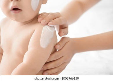 Woman applying body cream on her baby against light background