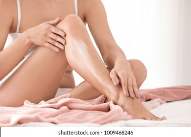Woman applying body cream on her leg in bedroom, closeup