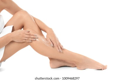 Woman applying body cream on her leg against white background, closeup