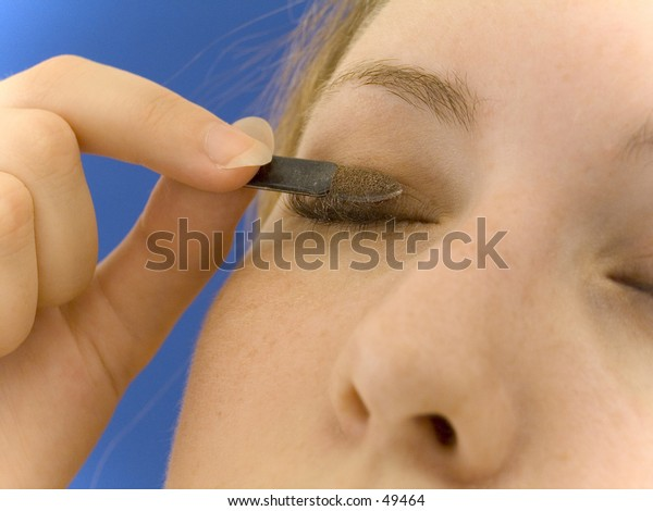 Woman applying brown eyeshadow, crisp focus in the center. Bright blue background.