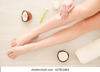 Woman applying coconut oil on legs, closeup