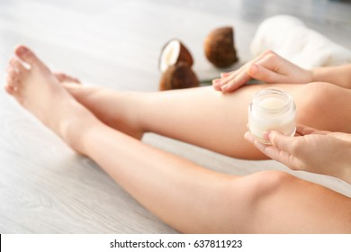 Woman applying coconut oil onto skin, closeup