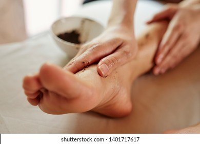 Woman applying coffee scrub on her foot and massaging it