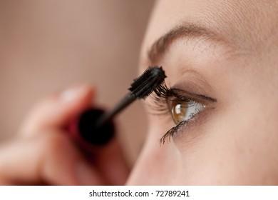 woman applying colorful makeup