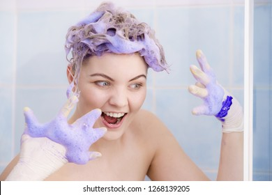 Woman applying coloring shampoo on her hair. Female having purple washing product. Toning blonde color at home.