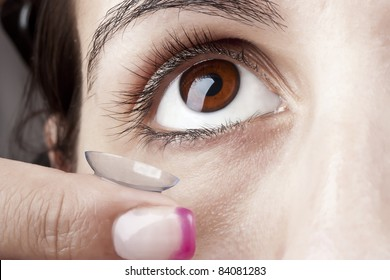 Woman applying a Contact Lens on her eye
