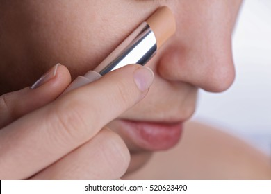 Woman applying corrector stick or concealer, cover dark circles under eyes . Beauty, make up concept