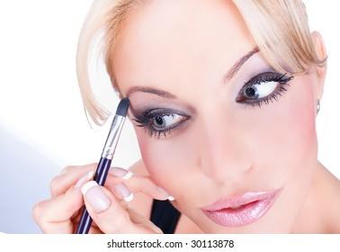Woman applying cosmetic with applicator, studio shot