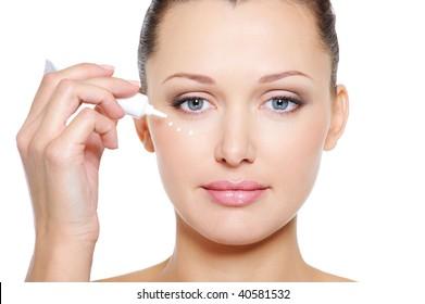Woman applying cosmetic cream on the beautiful face