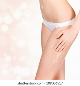 Woman applying cosmetic moisturizer cream on body, blurred background with a space for your message.