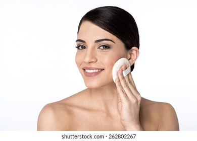 Woman applying cosmetic powder on face