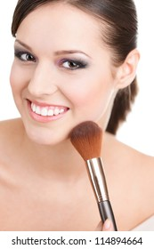 Woman applying cosmetics to her face with the help of cosmetic brush, isolated on white