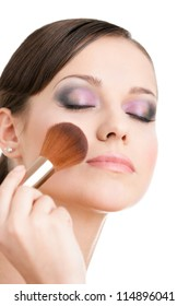 Woman applying cosmetics to her face with eyes closed with the help of cosmetic brush, isolated on white