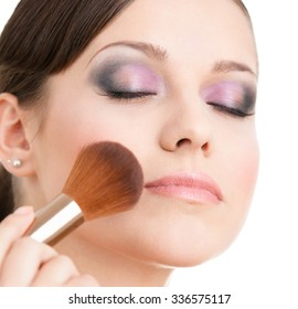 Woman applying cosmetics to her face with cosmetic brush, isolated on white