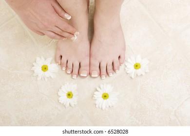 Woman applying cream to her feet