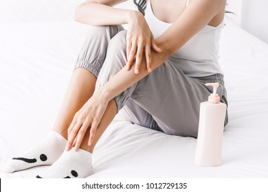 Woman applying cream on hand on bed