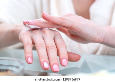 The woman applying the cream on her hands moisturizing and nourishing them with natural cosmetics close-up. Concept of hygiene and care for the skin