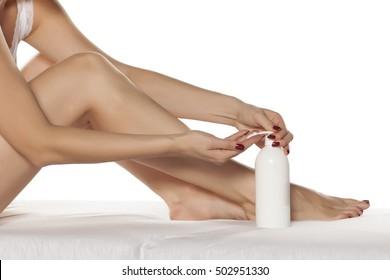 Woman applying cream on her beautifully cared legs