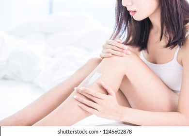 Woman applying cream onto her leg and shin at home