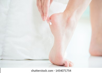 Woman applying cream onto her heel at home