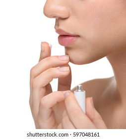 Woman applying cream onto lips on white background