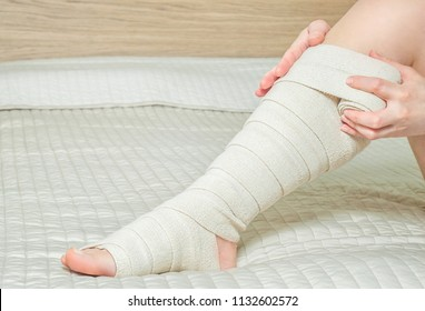 Woman applying elastic compression bandage as a thrombosis prevention after varicose surgery