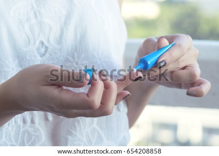 Woman applying eye cream by squeezing a little cream on her finger