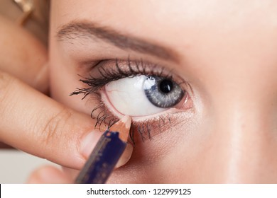 woman applying eyeliner on eyelid with pencil