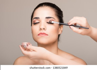 Woman applying eyeshadow with brush on model's eyelids in colored background
