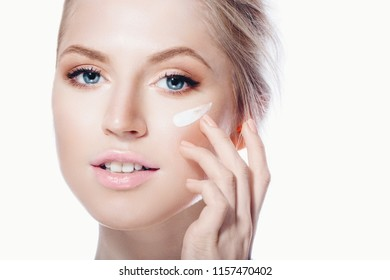 woman applying face cream white background