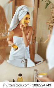 Woman Applying Face Mask. Wrapped In Bath Towel Model  Standing In Bathroom And Looking At Mirror. Facial Skin Covered With Beauty Product. Daily Routine For Healthy Derma.