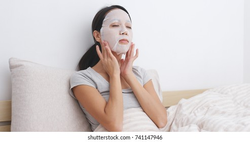 Woman applying facial mask on face and sitting on bed