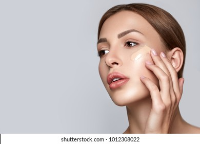Woman applying foundation. Skin tone cream lines on woman face. Beautiful woman portrait beauty skin healthy and perfect makeup. Space for text.