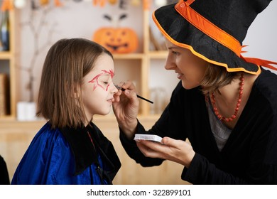 Woman applying Halloween make-up to face of her daughter