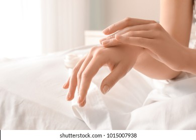 Woman applying hand cream at home, closeup
