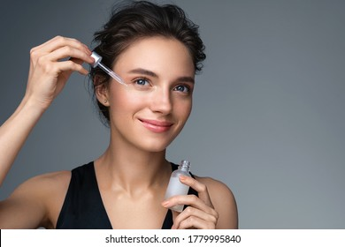 Woman applying  hyaluronic serum on her face with pipette. Photo of attractive woman with perfect makeup on gray background. Beauty concept