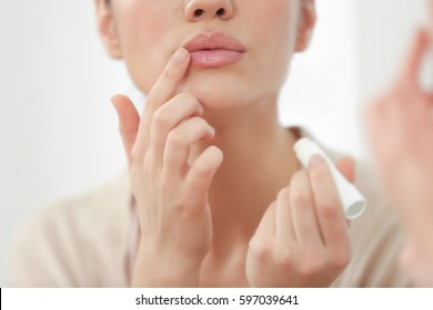 Woman applying hygienic lip balm near mirror