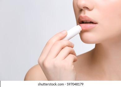 Woman applying hygienic lip balm on light background