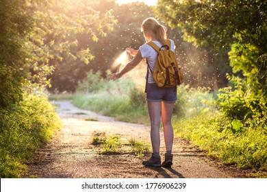 Frauen wenden Insektenabwehrmittel gegen Mücken an und ticken während des Naturwanderns auf ihre Hand. Hautschutz gegen Insektenbiss