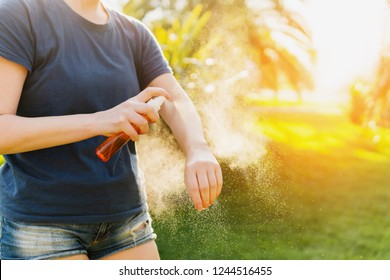 Woman applying insect repellent before forest hike beautiful summer day. Protecting from biting insects at summer. Active leisure.