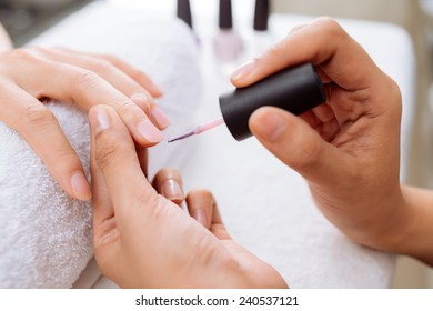 Woman applying light pink nail polish