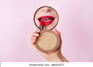Woman applying lipstick looking at mirror in hand. Red lips makeup closeup.