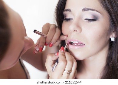 Woman applying make up for a bride in her wedding day