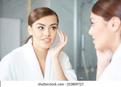 Woman applying make up with cosmetic brush